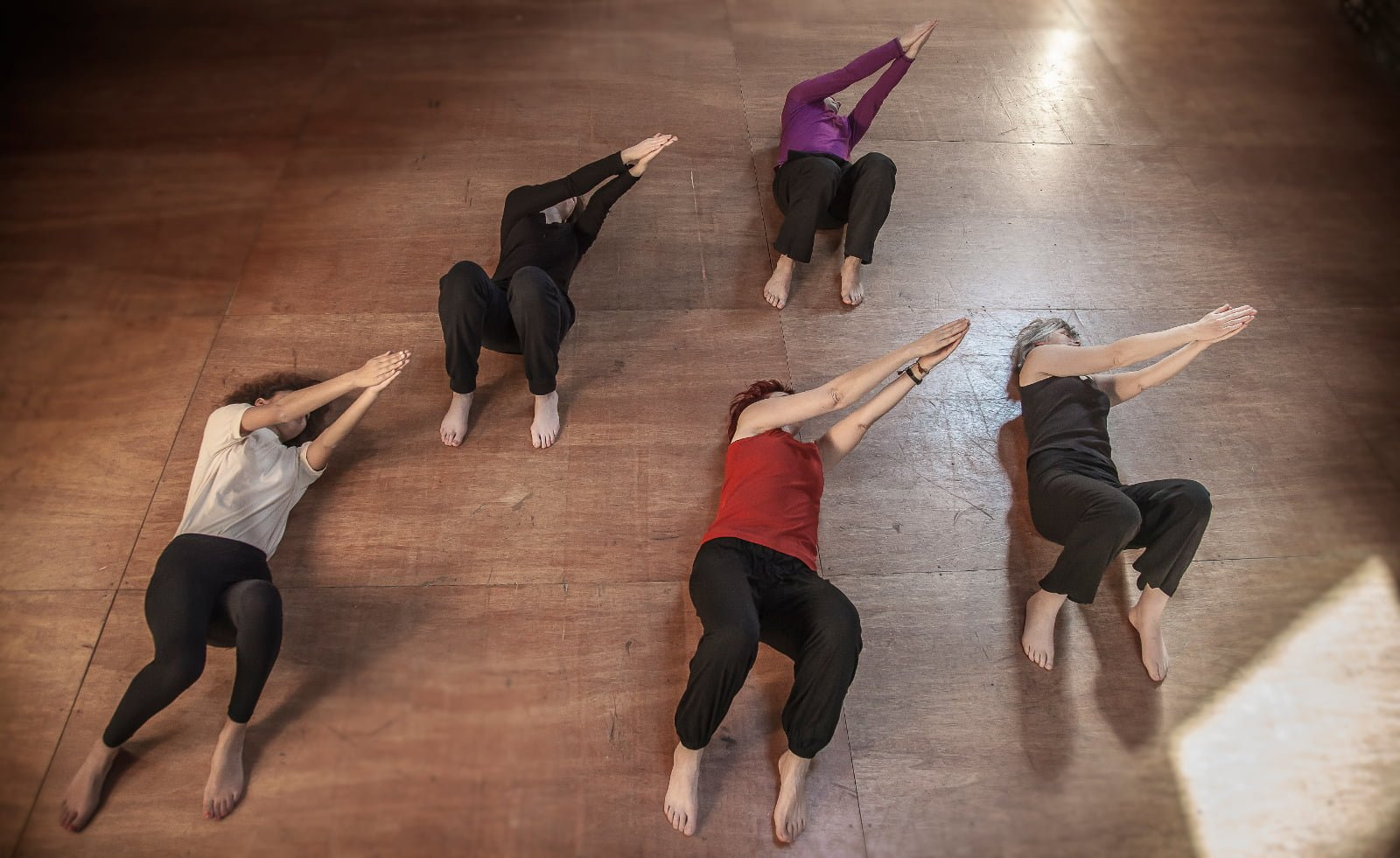 Small group of women lying on the floor, palms of hands together in the air, participating in a Feldenkrais exercise class for beginners in North Perth